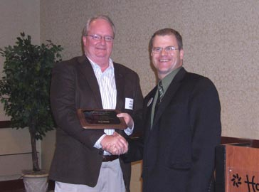 NCI Director presents a plaque to Brian Walker, in recognition of the Bronze Level sponsorship that Horizon Milling gave to the mill project.