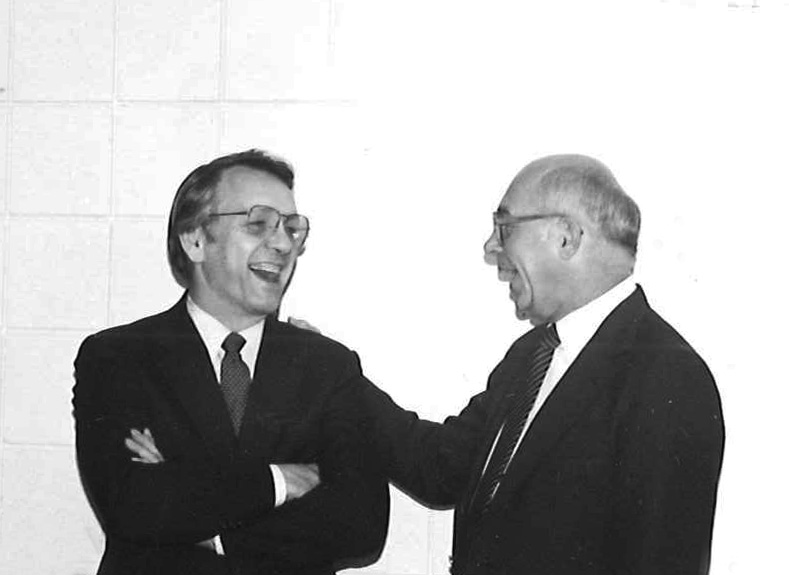 Former Governor George Sinner (first chairperson of the Northern Crops Council)  and Farmer Edwin Ross from Fisher, Minnesota (second chairperson of the Northern Crops Council), share a hearty laugh during the March 29, 1985, Northern Crops Council Meeting.