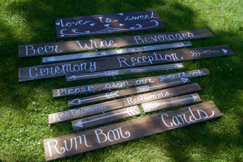 Hand painted signs for a wedding and reception on reclaimed wood