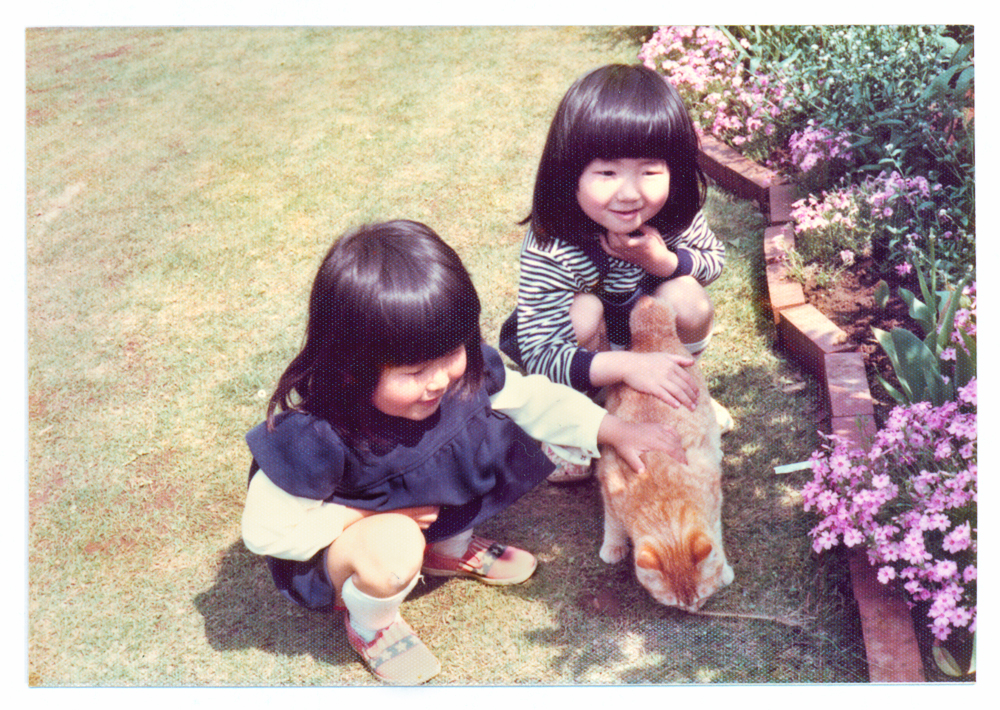 Seen here is Kyoko  in the  navy dress and in the stripe shirt is her  sister. The orange cat's name was Ichibei who was their main cat growing up, best cat ever...