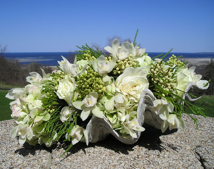 Flower arrangement in oyster shell for beach themed weddings
