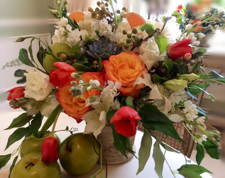 Happy orange roses, fruit & succulents floral centerpiece