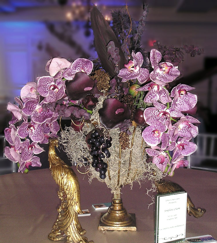 Floral arrangement with purple orchids & fruit