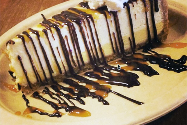 Our cheesecake is over the top when covered with chocolate & caramel drizzle