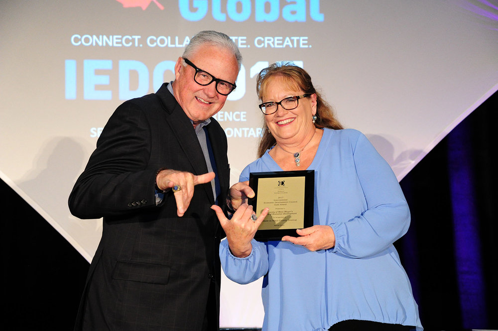 F. Michael Langley, FM, CEO of GREATER MSP, Minneapolis–St. Paul, MN, and 2017 IEDC Board Chair, presents Teena Rasmussen of the County of Maui Mayor's Office of Economic Development with IEDC's Gold Award.  Photo credit: IEDC