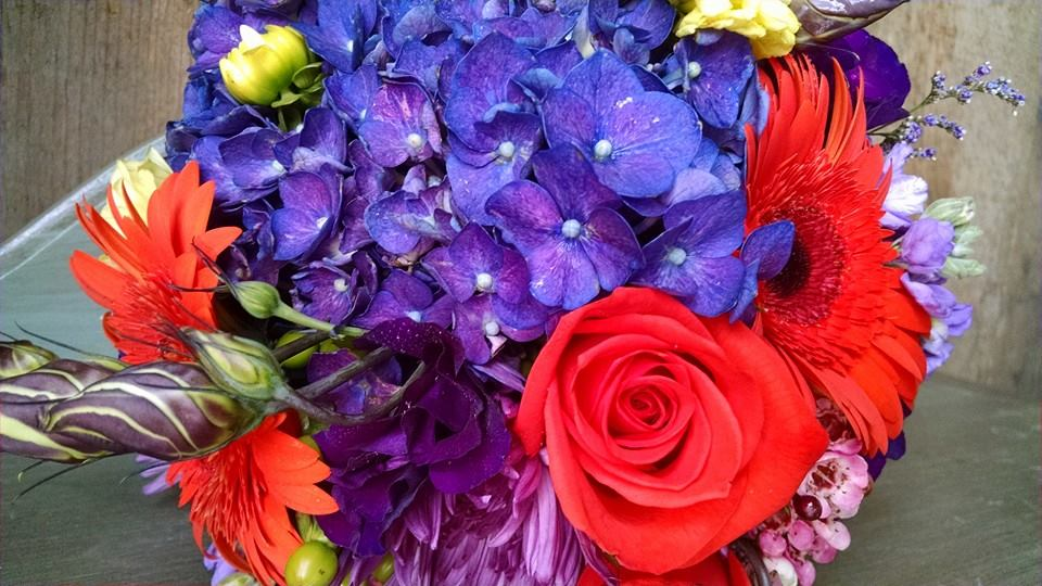 Bridal bouquet with purple hydrangea, lisianthus, fuji mums, oranges roses and gerbera daisies makes for a bold and bright statement on your special day.