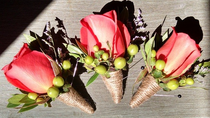 orange rose boutonnieres with green hypericum, blue misty and twine wrapped stems.