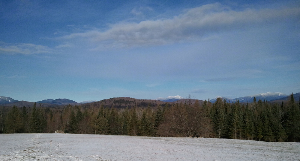 Adirondack mountains in winter where the author lived as a child. One particular mountain in the picture has significance in his four volume series.