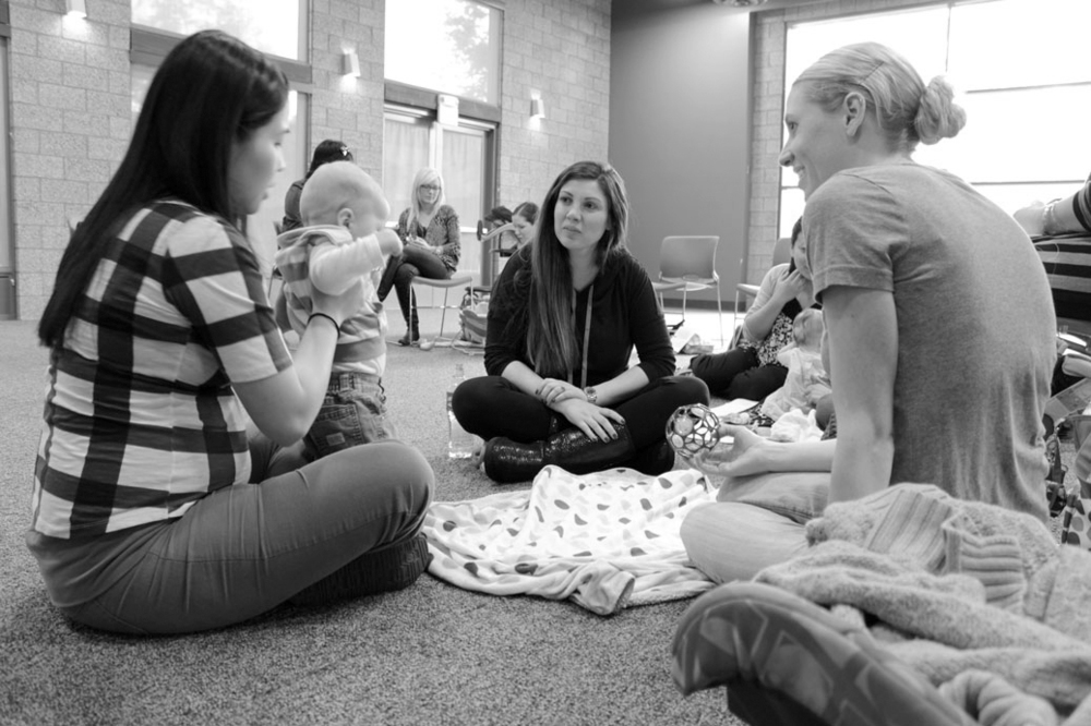 A mom-to-be at Boot CAmp holds a New Mom's BAby during the second-hour small group sessions. Expectant Moms are able to interact with the babies and ask the New Moms any questions they have.