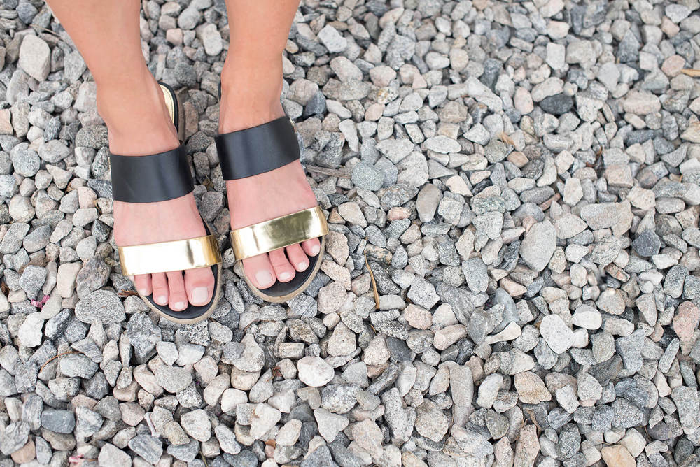 Gold and back sandals from a birds eye view.