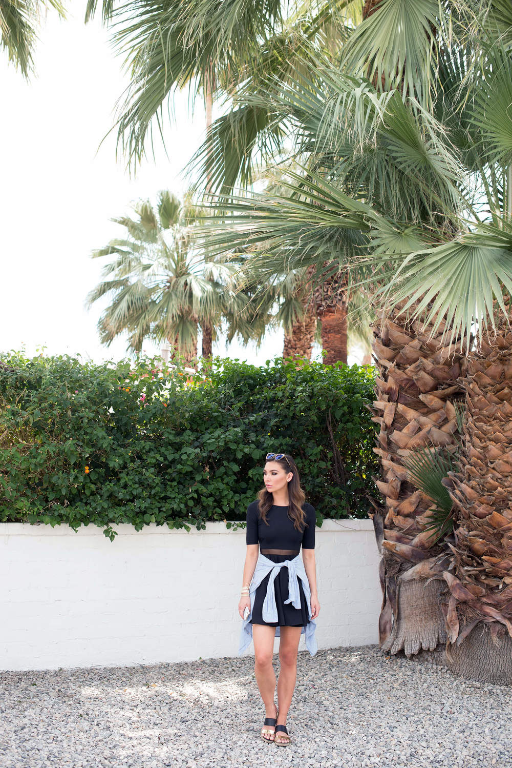 How to wear black for summer, layered with a button up shirt and sandals.