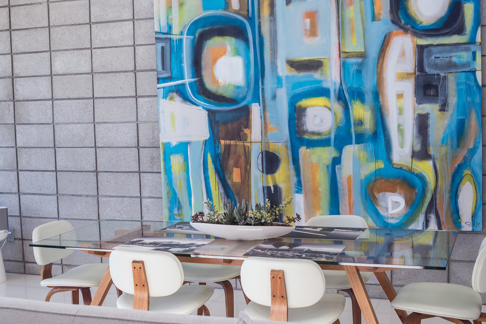 Concrete walls and massive abstract paintings with clean furniture lines.