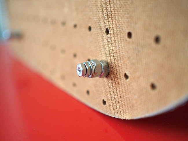 Pegboard wall spacer made with a screw, nuts, and washers.