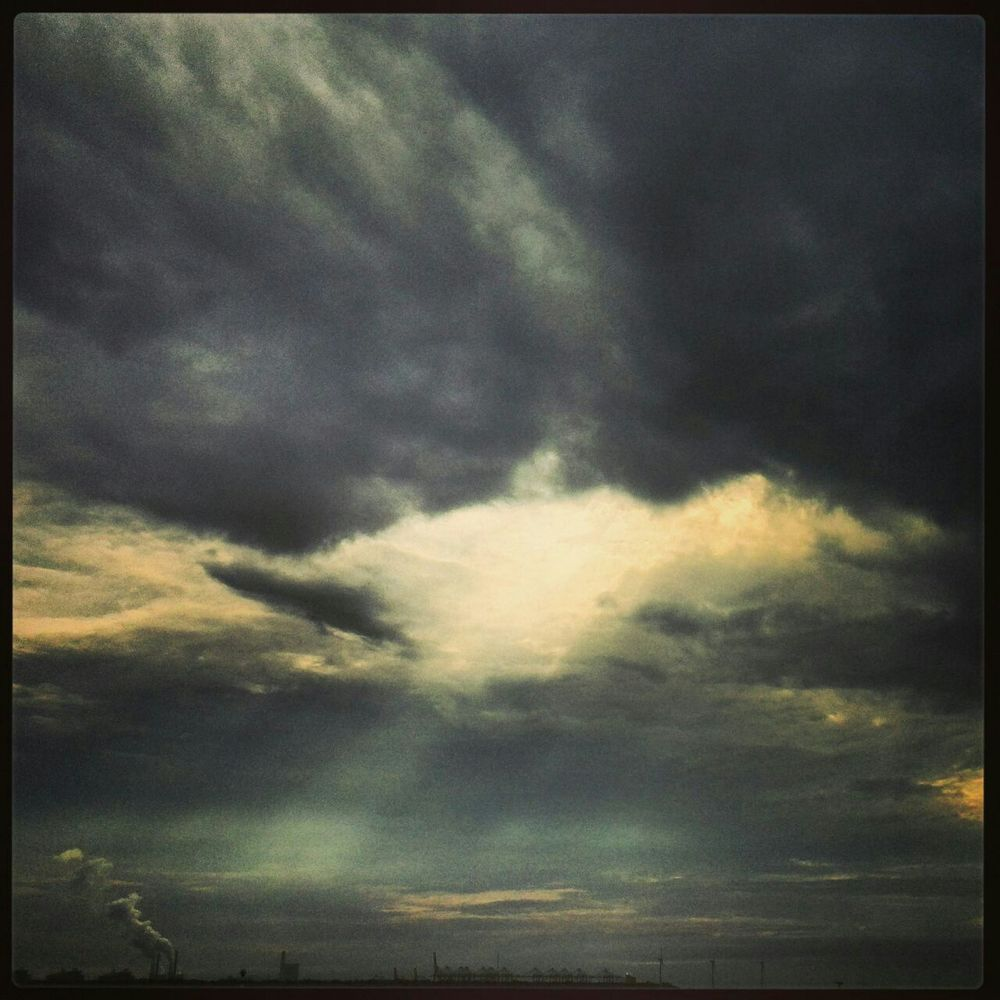 Beautiful nature sunday photo. Dark clouds accompanied by beautiful sunrays coming through the clouds.