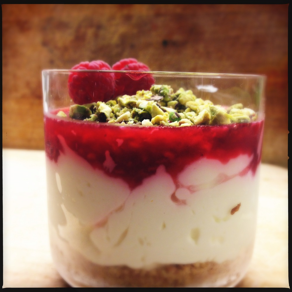 Desert: cheesecake in een glaasje met frambozen en pistachenootjes Desert: cheesecake in a glass with raspberries and pistachio