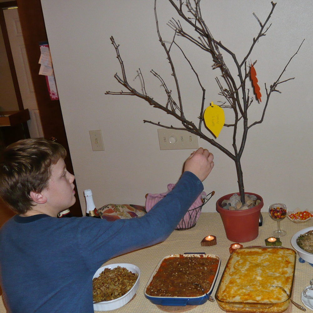 "My son adding his ""thankful"" to the tree."