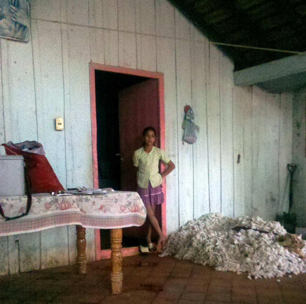 Girl with cotton pile and machete, rural Paraguay.