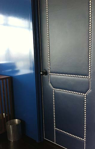 Leather upholstered door with nailhead trim
