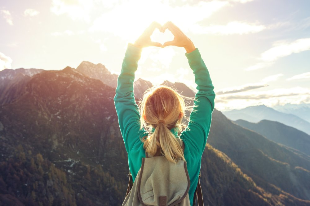 Young-woman-on-mountain-top-makes-heart-shape-finger-frame-638119094_5760x3840_Web.jpeg