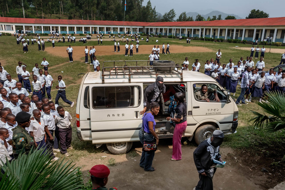 Students flock around a van that is delivering women scheduled to testify. For one week, the trial was held in a makeshift courtroom, set up in the auditorium of a Catholic school in Minova. Since victims could not afford a trip to Goma, more than 30 miles away, the court came to them.