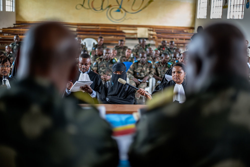 A victim testifies before the closed military tribunal. A member of the prosecution team holds a microphone up for her while a defense lawyer makes notes. The accused soldiers are seated in the rear. Victims are often extremely reluctant to step forward due to the stigma that Congolese society places on victims of rape. In Minova, only 47 victims testified.