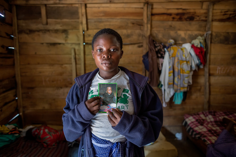 "A victim, 18 years old, holds a photo of her son, Arlain, who died as a consequence of the events of November 2012. FARDC attacked houses all over the  Minova, including a center for rape survivors, run by human rights activist and rape survivor herself, Rebecca Masika.  Many of the women at the center -- already victims of rape -- were raped again by the soldiers. ""When they pillaged, they also stole my son.  They put him in a suitcase and left.  We found him a few days later in the same suitcase, abandoned near our center.  He was so ill afterwards.  He died a month later."" Arlain was 1 1/2 years old and conceived from an earlier rape.  When his mother was 16, she was abducted by FDLR rebels from her home in Ngungu village, Masisi territory.  She was held captive for five months – fed and housed, but raped repeatedly by numerous FDLR soldiers.  In captivity, she had her first menstrual cycle, and became pregnant shortly afterwards.  She does not know which one of the men who raped her is the father of her now deceased child."