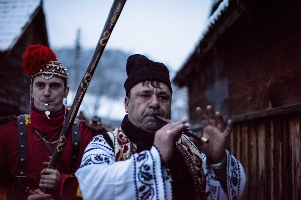 Dumitru Toloaca, the leader of a bear troupe from Laloaia village, marches through the alleys of Asău village. He is followed closely by his 'bear tamer' and troupe of bears, guiding them to private homes where they've been invited to perform. December 28, 2014. Asău village, Bacău County, Romania.