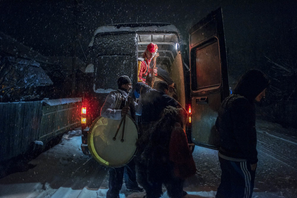 Toloaca's troupe piles into a van that will take them to the next village. In the days leading up to the New Year, troupes of bears dance their way into the night through a handful of towns and villages in the Trotuș Valley. December 28, 2014. Asău village, Bacău County, Romania.Asău village, Bacău County, Romania.