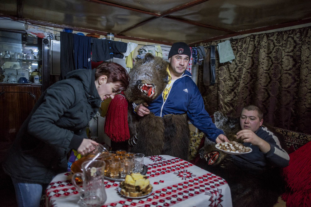 Cătălin Apetroaie, a bear in Toalaca's troupe, serves his fellow bears cubes pig fat, while his wife fills up glasses of homemade palinka liquor. The troupe has just finished performing at Apetroaie's home and is taking a rest before continuing to the homes of other patrons that have requested their visit. December 28, 2014. Laloaia village, Bacău county, Romania.