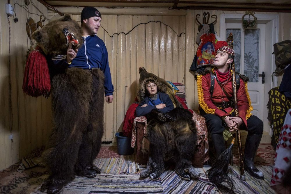 Cătălin Apetroaie chats on his porch with a young bear and Gabriel Hanganu, the 'bear tamer.'  The troupe, led by Dumitru Toloaca, has just finished performing for Apetroaie's family and are resting before they continue on to the homes of other patrons that have requested their visit. December 28, 2014. Laloaia village, Bacău county, Romania.