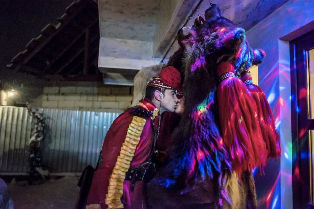 The 'bear tamer,' Gabriel Hanganu, sneaks a kiss from his fiancée, Anca, who has been waiting for him on Toloacă's porch, huddled for warmth in between bear skins hung up at the end of each night. December 28, 2014. Laloaia village, Bacău county, Romania.