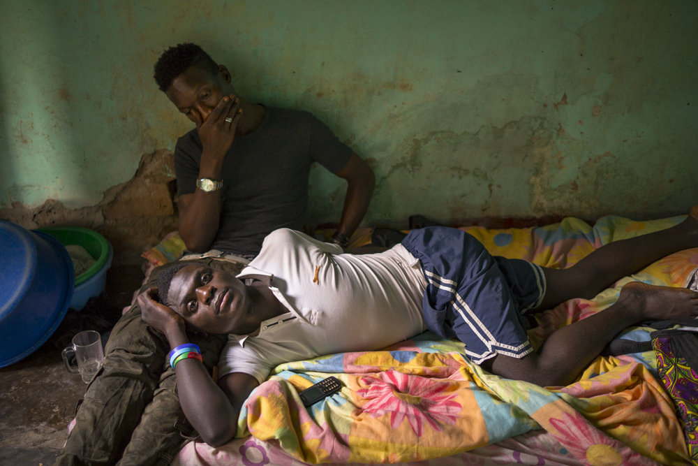 Jackson Mukasa lies on his bed, resting his head on the lap of his friend, Kim Mukisa, who has dropped by for a visit. The two were beaten and arrested in January 2014, accused of homosexuality. After 5 months in jail, their case was dismissed for lack of prosecution. After their release , they began life anew, having been robbed of their posessions. Mukisa, a clothing designer, also lost his atelier and shop in downtown Kampala. Kampala, Uganda. August 14, 2015.