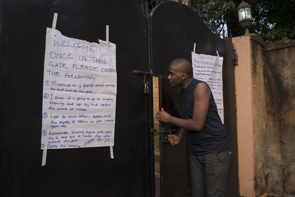 "The appointed gatekeeper opens the door to let in a member of the LGBT community. To ensure the security of particiants, events were held in ""secret,"" at private locations that were disclosed to members of the LGBT community and their supporters just one or two days before an event. Kampala, Uganda. August 6, 2015."
