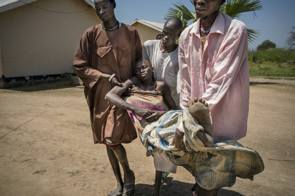 "Thirty -two year old Arek Nuoi, mother of four, is carried unconscious by her three brother-in-laws from the consultation room to the hospital bed at Panthou health care center. There, she will receive urgent treatment for acute malaria.  ""Yesterday, we were here [in Panthou] for market day, and she was okay,"" began one of her brother-in-laws. ""Last night she had a headache and then body pain,"" continued her mother. ""This morning, I went to collect the local tree,"" she explained, referring to the traditional plant medicine for headaches and aches.  When she returned, she found Arek collapsed and vomiting.  The family tied a chair onto a bicycle and placed Arek in the chari. They then pushed it all the way from their home village of Maper to the Panthou health center. The journey took one and a half hours. They have a mosquito net and always sleep in it, but none of them knew how one contracts malaria. Panthou health care center is the only one in Aweil South county and is currently treating about 150 malaria patients per day. They just received a supply of ACT oral medication for malaria, which had ran out on August 17. It will likely run out in one or two weeks. They have quinine but not a lot so they reserve it for serious cases. They have no RDT (rapid detection tests), so diagnosis is only done clinically based on sypmtoms observed."
