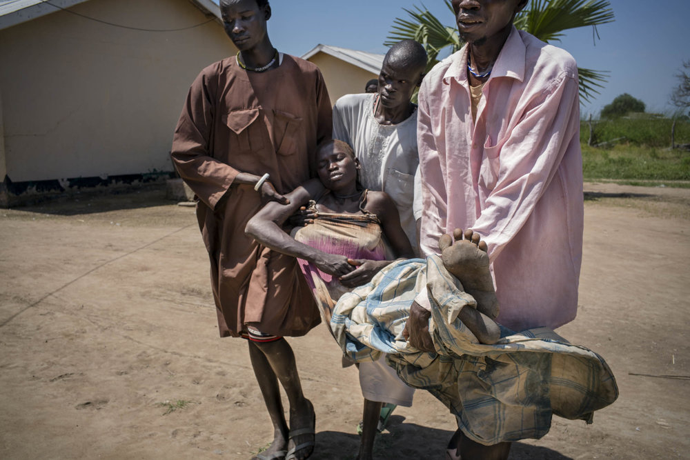 Arek Nuoi, 32, is carried unconscious by her three brother-in-laws to a ward at a government-run health care center, where she will receive urgent treatment for acute malaria. Her brother-in-laws transported Arek from their home village by placing her in a chair that they tied on top of a bicycle, and pushing the bicycle for one and a half hours to reach the health care center. South Sudan is host to one of the deadliest conflicts in the world, yet in 2015, malaria killed more people than bullets. Across the country, 2.28 million cases of malaria were reported. Panthou, Northern Bahr el Ghazal, South Sudan. October 14, 2015