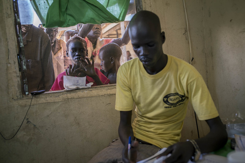 Patients wait to receive medicine at a health care center in Panthou village. Located in a remote rural area, the center was the only place in Aweil South county where patients might be able to receive free treatment and medicine for malaria. Only two staffs - both medical assistants - at the health care center are qualified to diagnose and treat patients. They treated approximately 150 malaria patients per day. The center had just received a supply of ACT oral medication for malaria, which had been out of stock for two months. The new supply was predicted to last one or two weeks. The only other medication in stock was quinine, but there was so little left that it was reserved for serious cases only. The center had no RDTs (rapid detection tests), so diagnosis was only done clinically based on symptoms observed. South Sudan is host to one of the deadliest conflicts in the world, yet in 2015, malaria killed more people than bullets. Across the country, 2.28 million cases of malaria were reported. Panthou village, Northern Bahr el Ghazal state, South Sudan. October 14, 2015