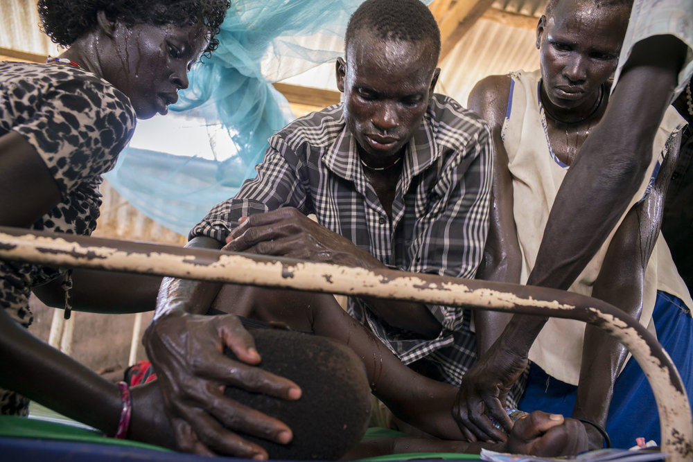 The family of eighteen year-old Abuk Akuoc, semi-conscious and letting out cries of pain, holds her still in preparation for an IV of quinine, life-saving medication for malaria, at a health care center in Panthou, a remote village in Northern Bahr el Ghazal, the poorest state in South Sudan. The country is host to one of the deadliest conflicts in the world, yet in 2015, malaria killed more people than bullets. Across the country, 2.28 million cases of malaria were reported. The lack of accessible health care facilities and drug shortages were particularly apparent in Northern Bahr el Ghazal. Many traveled hours or days and arrived to a medical facility too late, now suffering from cerebral malaria, an advanced condition in which the brain is affected, or already dead. Panthou village, Aweil South county, Northern Bahr el Ghazal, South Sudan. October 14, 2015