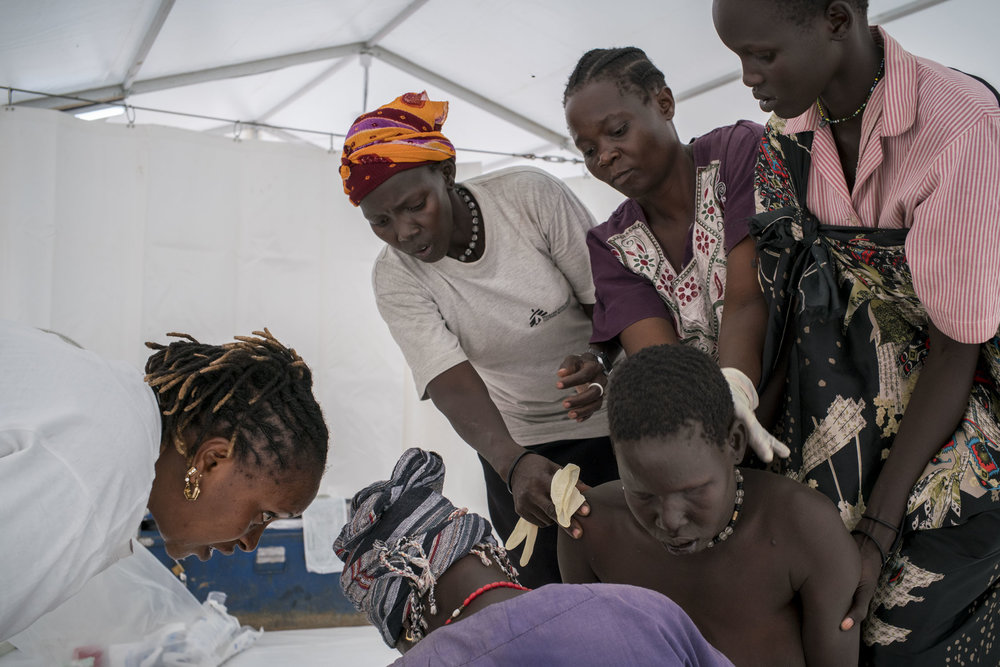 After an extremely difficult labor, a woman delivers her eighth child on her knees, assisted by a midwife, Rebecca, and her four assistants in a MSF hospital tent in the internally displaced persons (IDPs) camp in Bentiu. South Sudan has the highest maternal mortality rate in the world, in part due to the lack for health care facilities coupled with one of the highest fertility rates in the world -- after six children, giving birth becomes high risk. Rebecca said she had never seen anyone deliver on her knees before, and that the infant was not breathing or suckling as a newborn should, suggesting possible birth defects. The camp at Bentiu had a population of over 120,000, making it the second largest city in South Sudan. Bentiu Protection of Civilians (PoC) camp, South Sudan. October, 2015