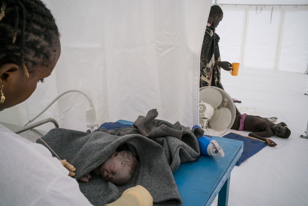 A midwife tends to a newborn who is not breathing or suckling as normally expected, suggesting birth defects, while his mother lies collapsed on the floor of the MSF hospital tent after an extremely difficult delivery. After six children, giving birth becomes high risk, and this is her eighth child. South Sudan has the highest maternal mortality rate in the world, in part due to the lack for health care facilities coupled with one of the highest fertility rates in the world. This MSF hospital served people displaced by the country's civil war and living in the Protection of Civilians (PoC) camp in Bentiu. The camp at Bentiu had a population of over 120,000, making it the second largest city in South Sudan. Bentiu PoC camp, South Sudan. October, 2015