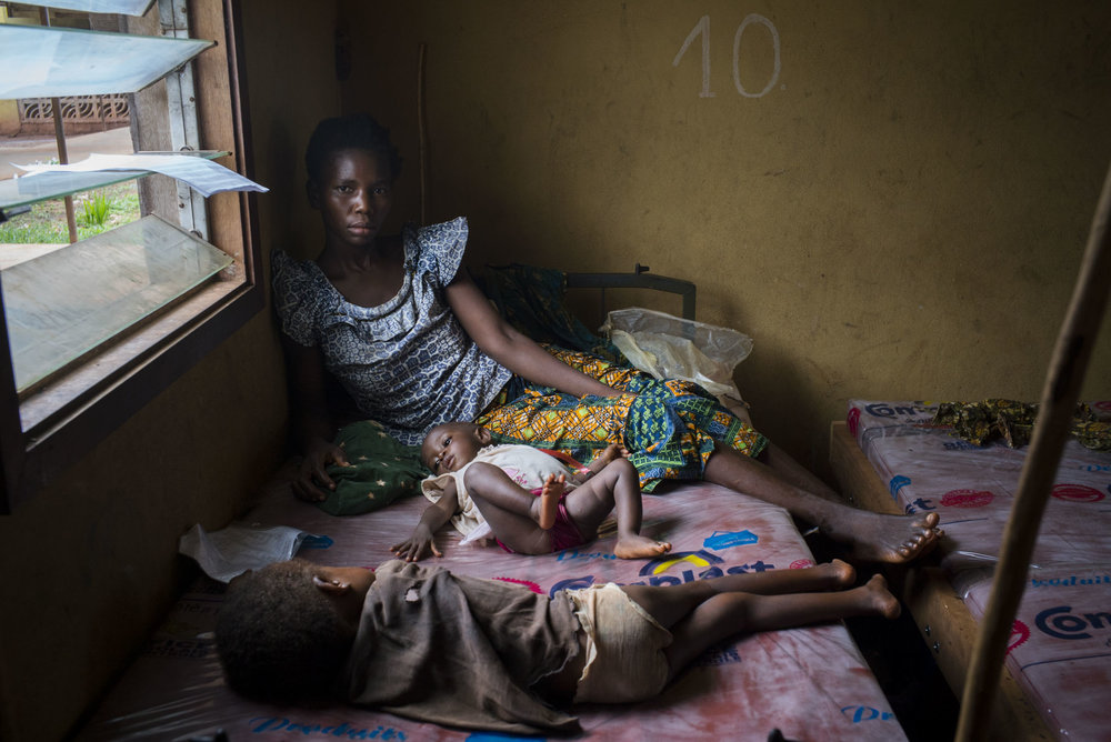 Madeleine Ngimambi, sits with her 7-month old daughter, Madeleine Pemu, who is receiving treatment for malnutrition in the MSF wing of the hospital in Monga, a town in a remote region of northern Democratic Republic of the Congo (DRC). Madeleine arrived to the hospital with both her daughter and son, after traveling 20 km on foot from their village, Faka. MSF was present at the hospital with the primary purpose of responding to an existing measles epidemic; however, they found many of the children admitted to their wing suffered from malnutrition. Monga, Bas-Uele province, Democratic Republic of the Congo. May 26, 2016