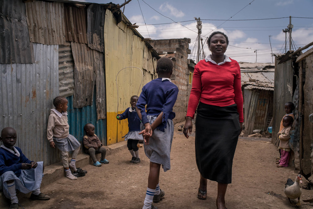 A teacher walks past children at a school (not Bridge) in Mathare slum area of Nairobi. September 19, 2016. Mathare slum, Nairobi, Kenya.