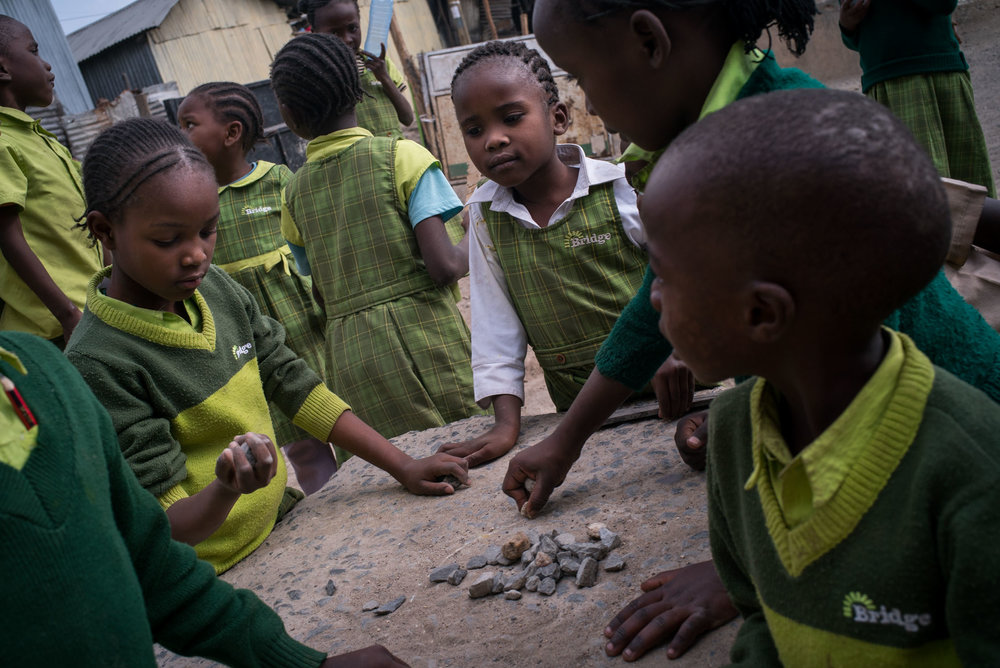 Students with small stones in the yard of a Bridge school in Mukuru slum. September 20, 2016. Mukuru, Nairobi, Kenya.