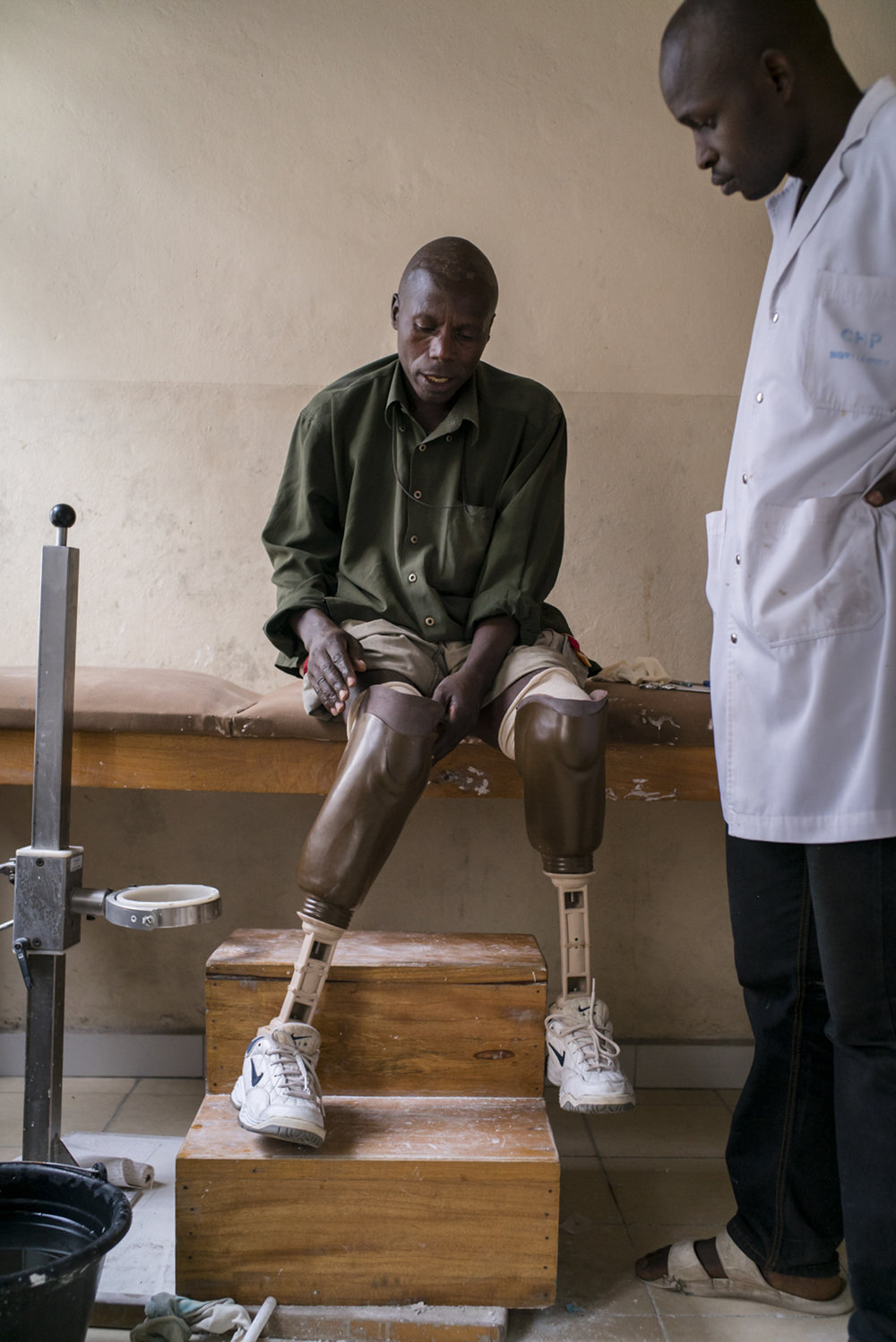 Augustin Semayinga Rukara, 51, a double amputee and father of eight, he puts on his prosthetic limb at a doctor's office. Augustin's village of Mpati, in Masisi territory of North Kivu,was attacked in June 2013 and he lost his right leg after he was hit by a bullet. In October of that year he received his first prosthesis from the ICRC. In March 2016, his village was attacked again, and this time fighters shot Augustin in the left leg as he fled for his life. In July 2017, Augustin's second leg had to be amputated. With a second prothetic leg from the ICRC, he was able to walk again. Centre pour Handicapes Physiques Shrika La Umoja, Goma, North Kivu, Democratic Republic of Congo. August 30, 2017.