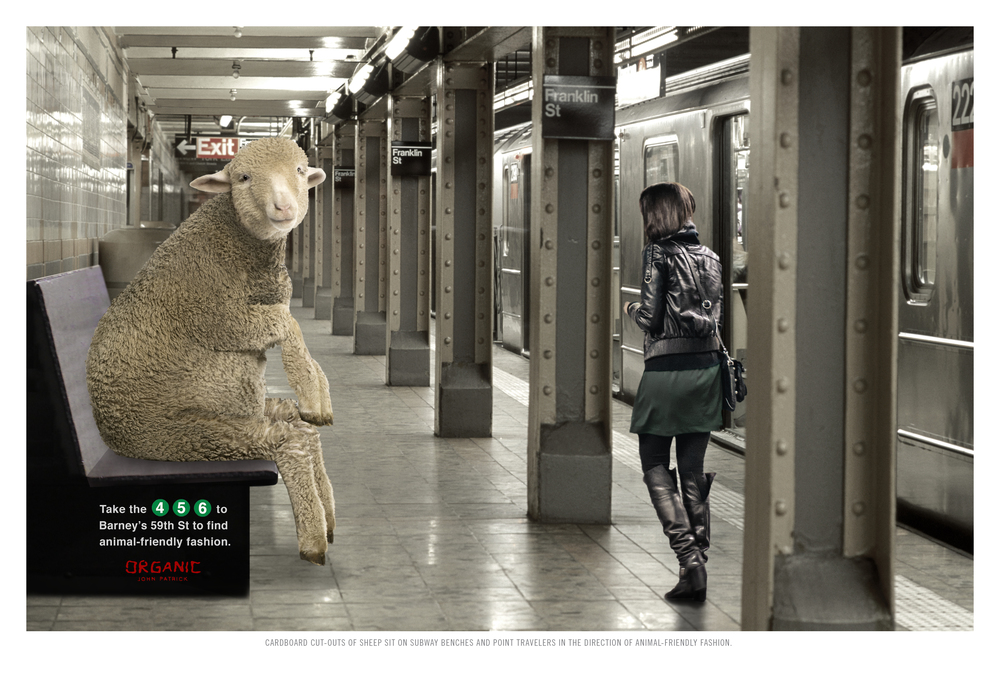CARDBOARD CUT-OUTS OF SHEEP SIT ON SUBWAY BENCHES AND POINT TRAVELERS IN THE DIRECTION OF ANIMAL-FRIENDLY FASHION.