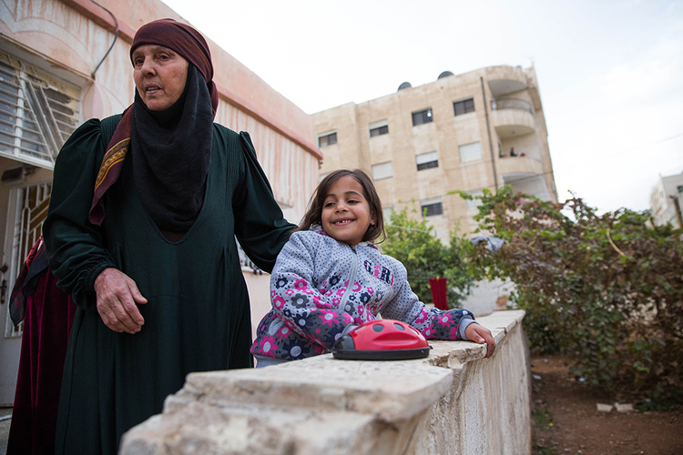 A grandmother and her granddaughter in the Middle East. They are part of a larger family of 14 who live in an apartment. They came as refugee from the Syrian war, but managed to leave early enough to where they can benefit from having a home for their family and even able to provide education for their children.