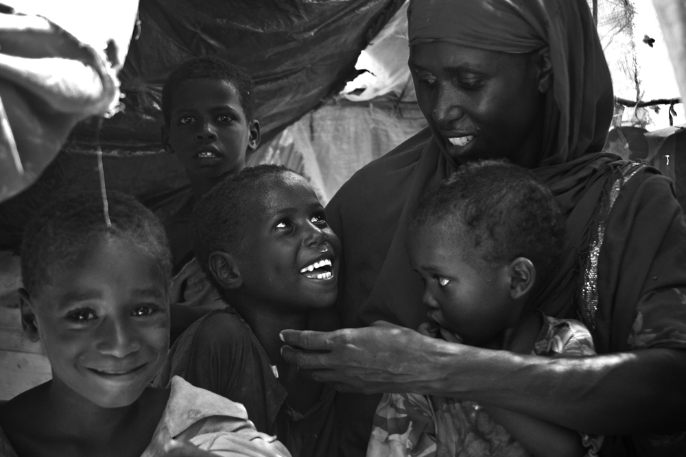 A mom, Tamiima, and her 4 kids inside their tent in a refugee camp in the Horn of Africa. They have been displaced because of drought and war and now the 4 of them live inside this small tent, but even through tough times they find time to smile and play.
