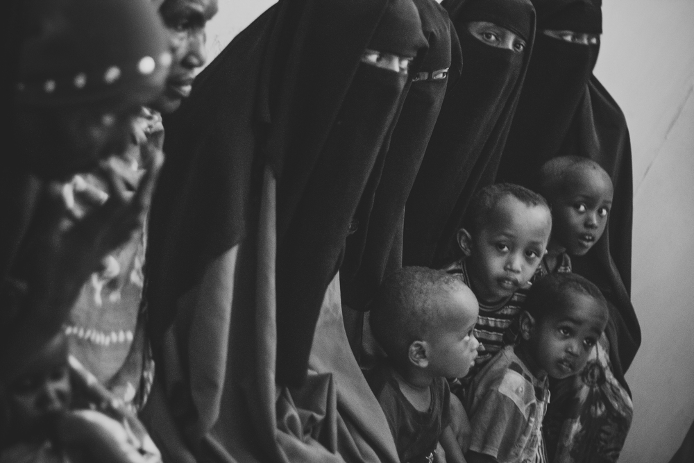 Mothers along with their children wait to receive medical aid in a war-torn city in the Horn of Africa.