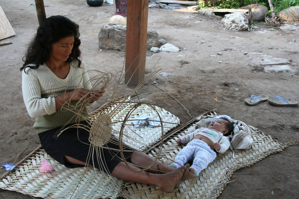 A woman in the Peruvian high jungle watches over her baby as she makes baskets for the local market.