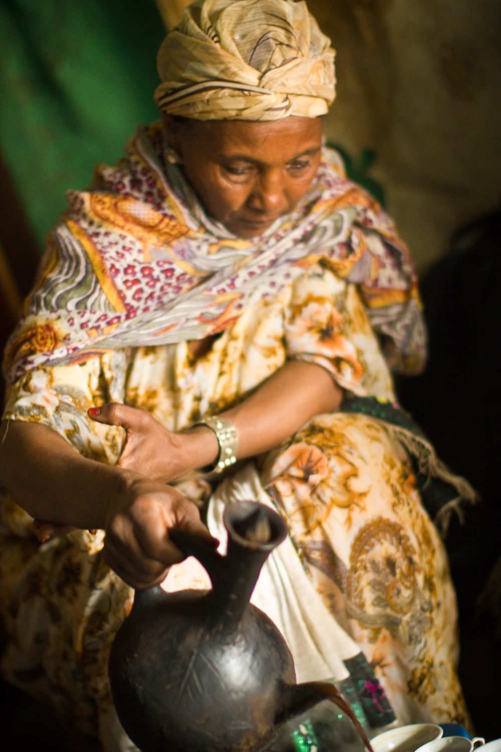 A mother makes traditional Ethiopian coffee for our team of guests who employed her son for the day as a tour guide.