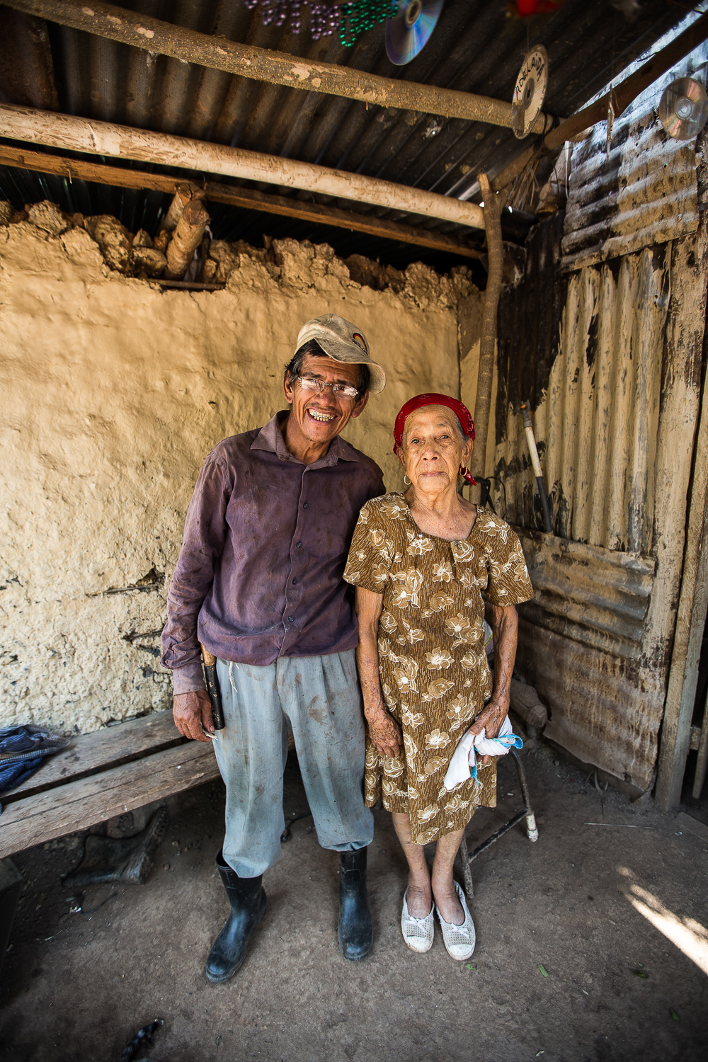 Domitio stands with her son in their house in Honduras.
